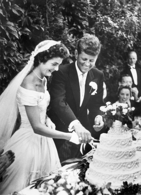 """PX 81-32:61 12 September 1953 John F. Kennedy and Jacqueline Bouvier Kennedy cut their wedding cake, Newport, Rhode Island, 12 September 1953. Please credit """"Toni Frissell Collection, Library of Congress"""" for the image."""